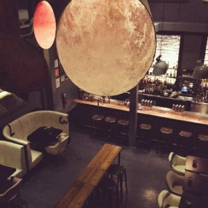 A sexy den laden with brick, and dark wood interior. Giant ship pieces from salvaged materials adorn the subterranean bar. Spherical light fixtures hang gently from the ceiling, providing a warm glow reminiscent of the moon.